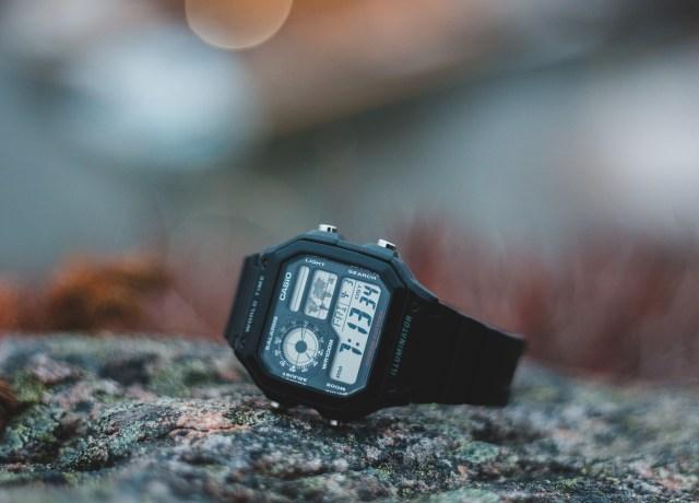 black digital watch on gray rock