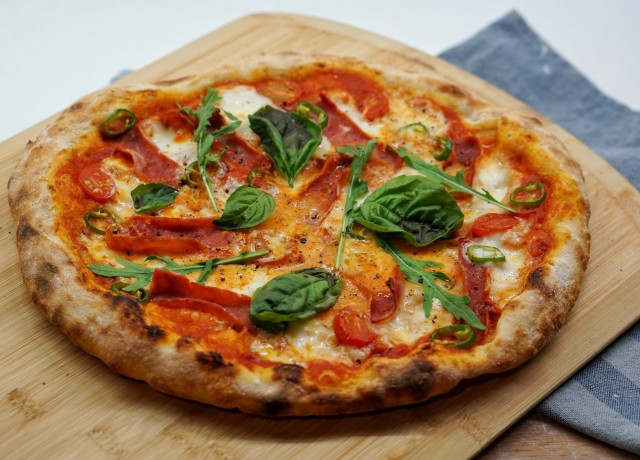 pizza with green leaves and red sauce