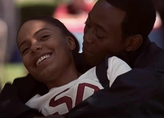 Monica e Quincy se abraçando no gramado da universidade.