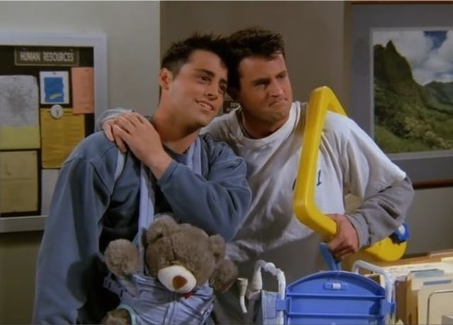 Joey and Chandler lean on each other while each holding a baby toy ( Joey is wearing a baby sling with a teddy bear in it and Chandler is holding a broken square scooter).