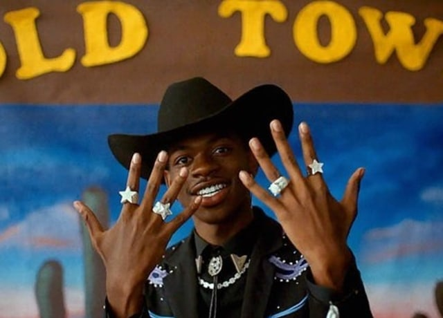 Lil Nas showing his star shaped rings, while also wearing a cow boy hat