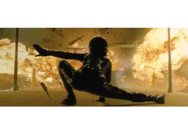 Imagem do filme, Trinity é vista de costas com uma roupa preta, uma perna estendida para o lado. Uma explosão acontece na frente dela.