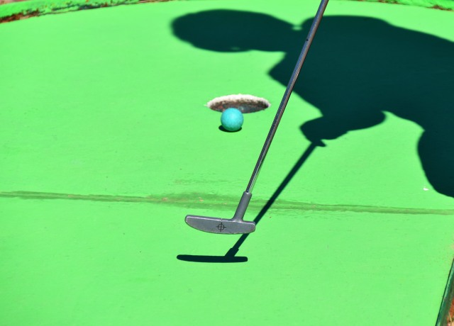 person golfing and ball about to shoot in hole