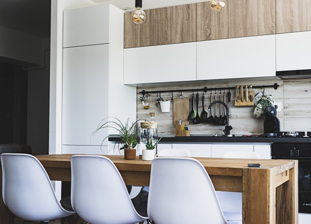 brown wooden dining table with white chairs near kitchen
