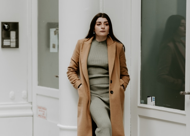 woman in brown coat and gray pants standing on white concrete staircase