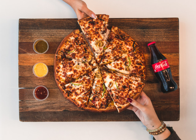 eight sliced pizza with Coca-Cola bottle beside