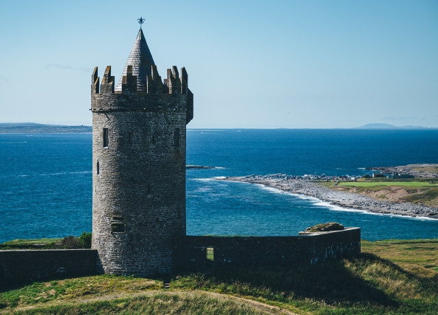 gray castle tower on mountain shore during day