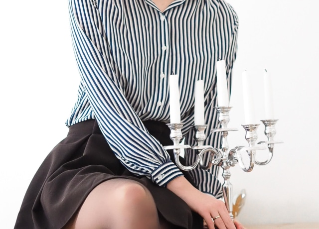 woman in black and white striped long sleeve dress sitting on brown wooden table