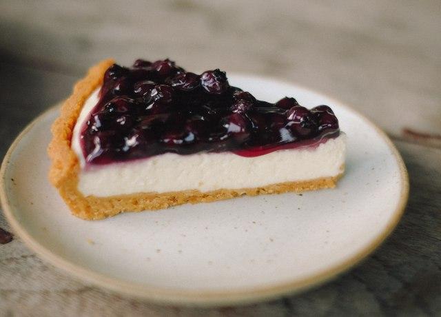 slice blueberry cheesecake pie on white ceramic plate