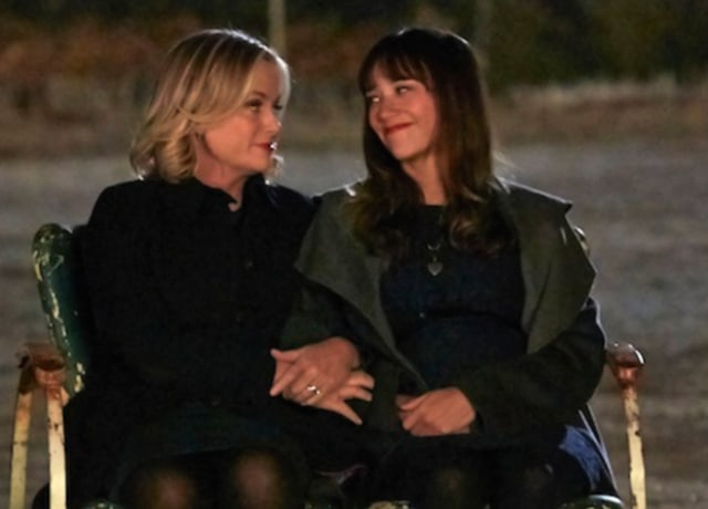 Leslie and Anne hold each other's arms as they sit next to one another.