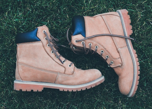 pair of brown-and-black work boots on green grass field during daytime
