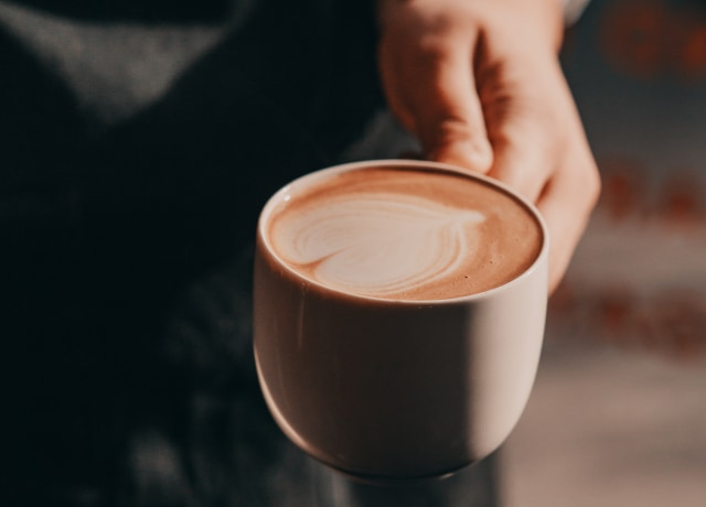 person holding brown teacup