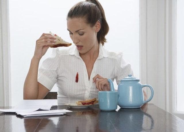 Foto de uma mulher sentada à mesa, com metade de um sanduíche de pão de forma e geleia na mão. Ela olha para sua camisa branca, suja de geleia.