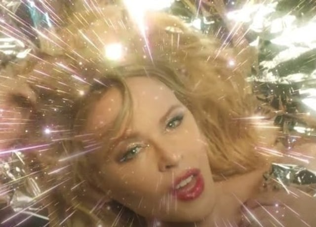 Kylie Minogue with disco lights emerging around her face