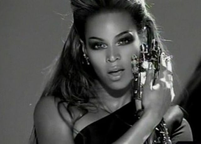 Beyoncé wearing a bejewelled glove on one hand and touching it with the other