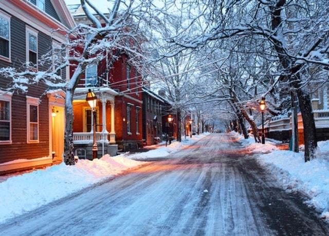 Rua iluminada e cheia de neve.