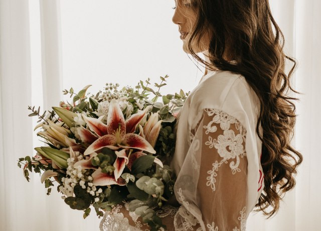 woman in white dress holding bouquet of flowers