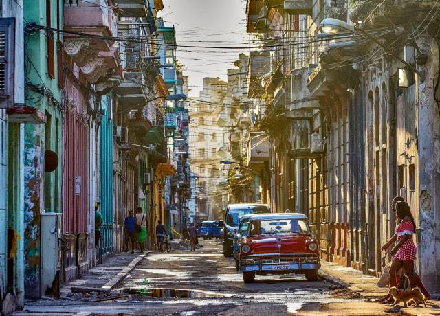 red van on road in between buildings during daytime