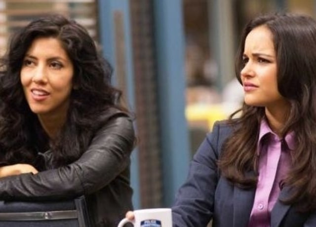 Amy shoots a look of confusion while Rosa smiles slightly.