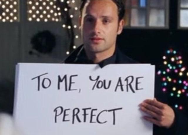 """Mark segurando um cartaz na frente da casa da Juliet. Diz: """"Para mim, você é perfeita"""""""