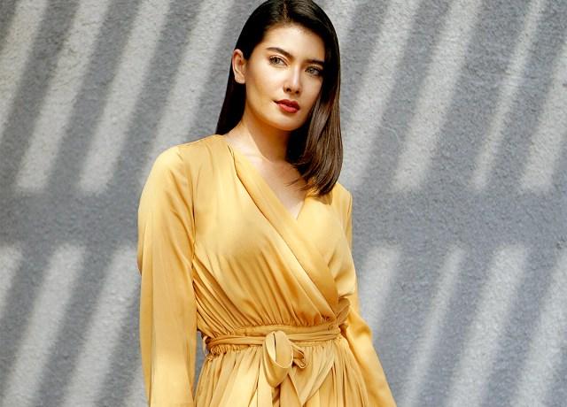 woman in brown long sleeve dress standing beside gray wall