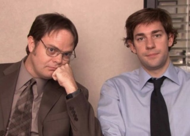 Jim and Dwight sit side by side while staring blankly into the camera.