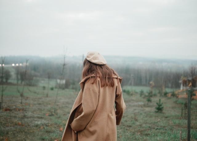 woman wears brown coat