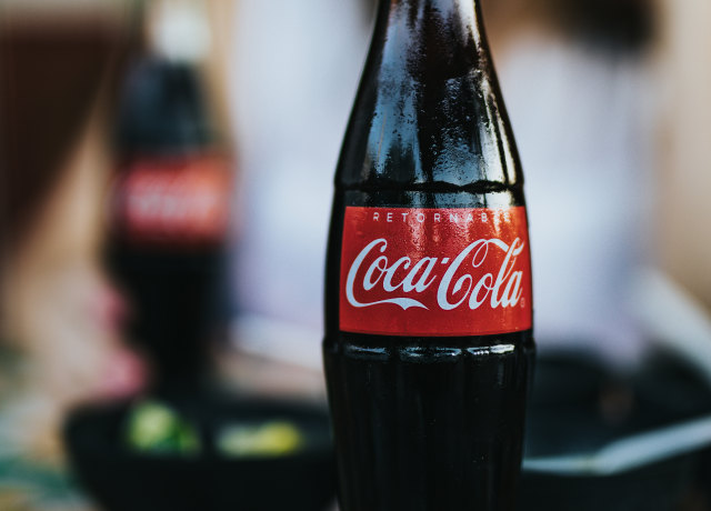 opened Coca-Cola glass bottle with straw