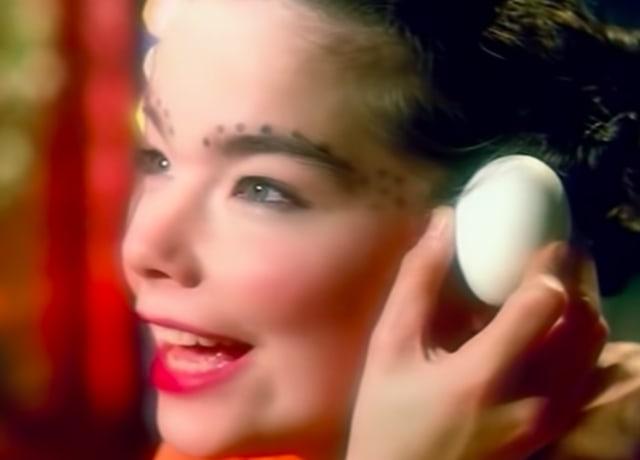 """Imagem do clipe da música """"Venus as a Boy"""" da Björk. A imagem mostra o rosto da cantora enquanto ela canta e segura um ovo de galinha próximo do rosto dela."""