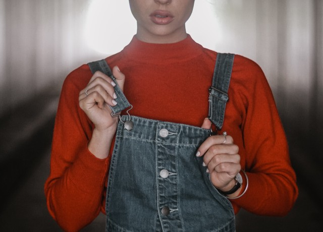 woman holding her dungaree dress