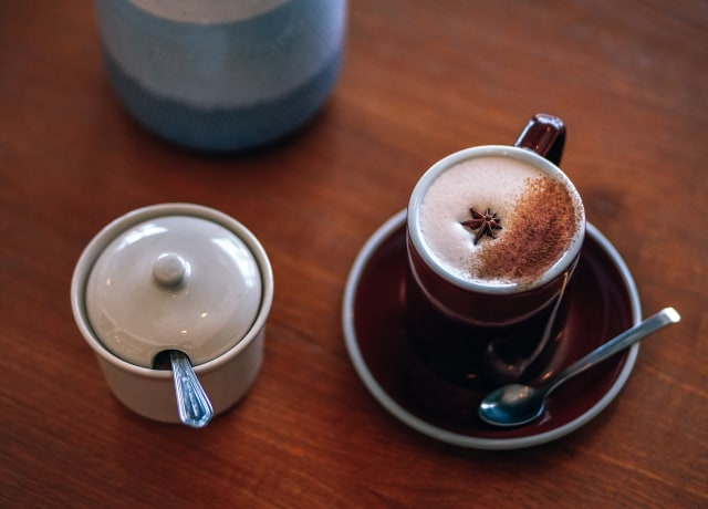 coffee mug on saucer beside canister