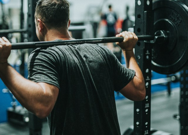 man in black t-shirt carrying barbell