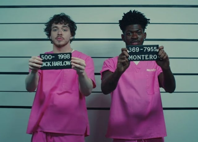 Lil Nas and Jack Harlow in prison uniform, showing their slates to the camera