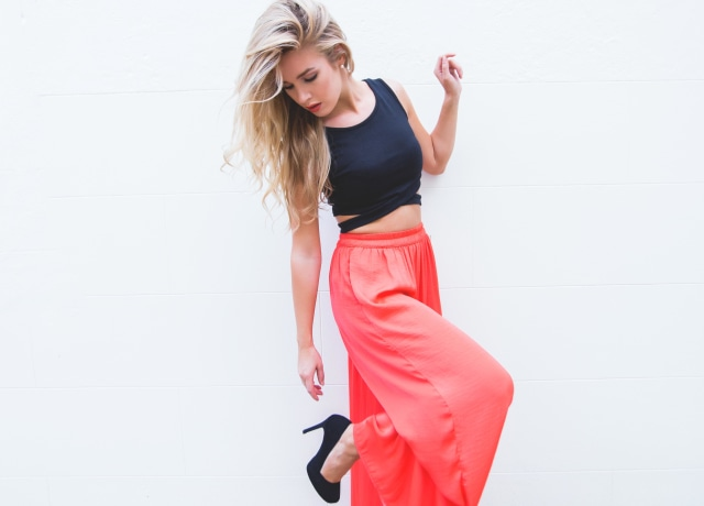woman wearing black crop top and red silt skirt