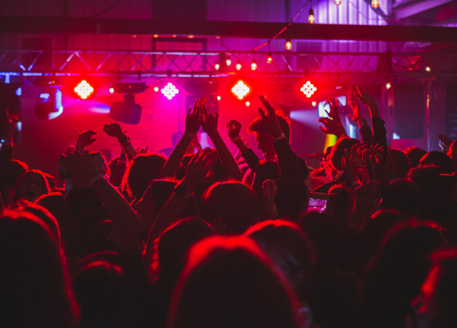 people standing on stage with lights turned on during nighttime