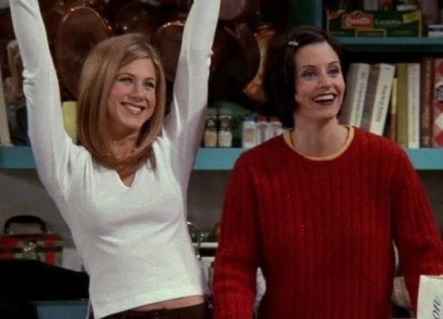 Rachel smiles while holding her arms in the air and Monica is mid laugh.