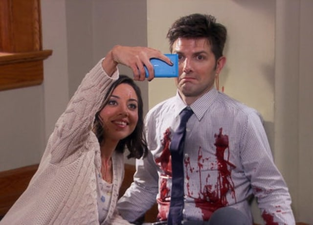 April Ludgate holds out her phone to take a selfie as Ben Wyatt stands with paint spattered on his shirt.
