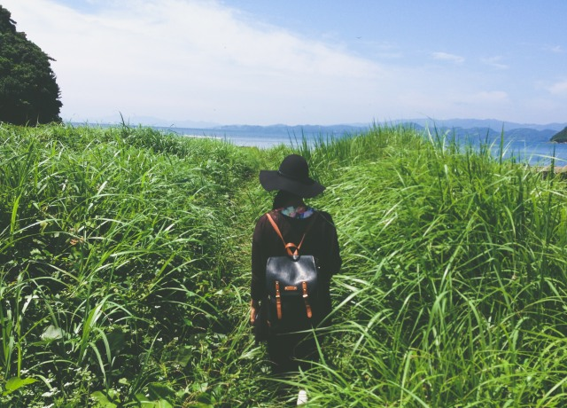 woman standing in the middle of green grass near sea at daytime