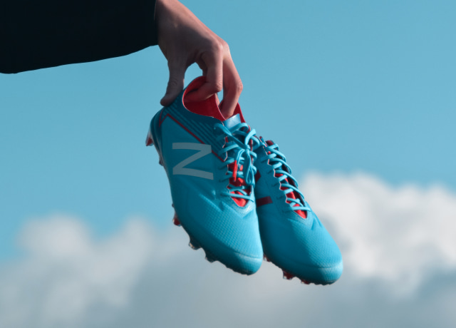 person holding pair of blue New Balance cleats