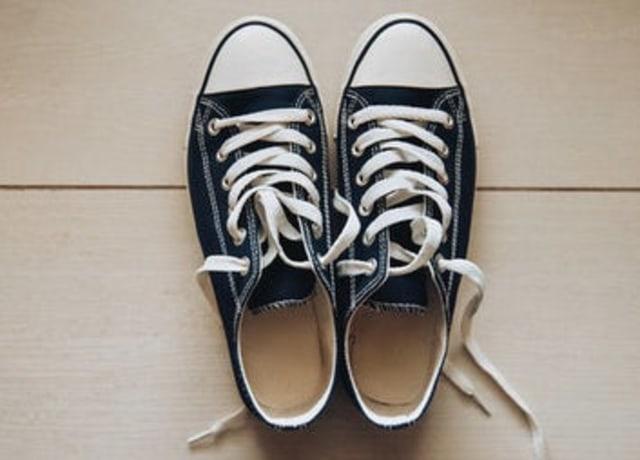 Tênis pretos largos, com cadarços brancos e ponta branca