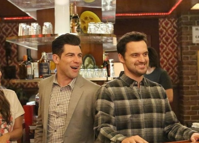 Nick and Schmidt smile brightly while standing behind the counter in the bar they own.