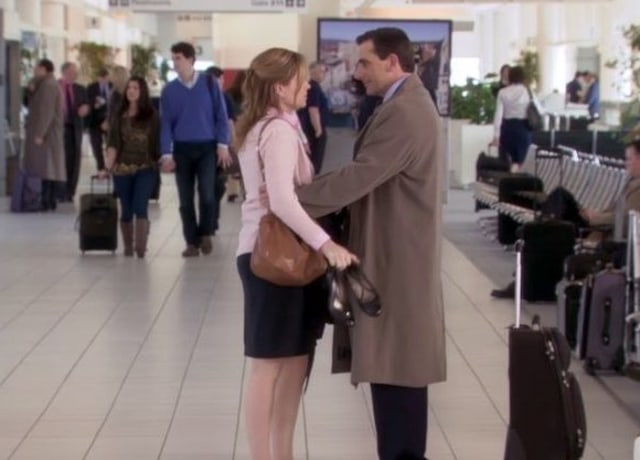 Michael holds Pam's arms as they stand in a busy airport.