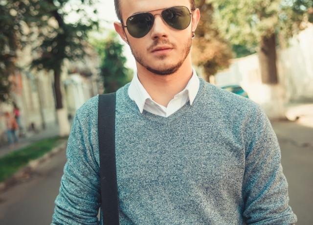 man in blue sweater wearing black sunglasses