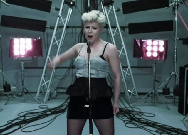 Robyn standing and singing into the microphone with stage equipment in the background