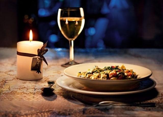 Jantar à luz de velas, não é possível identificar a comida no prato