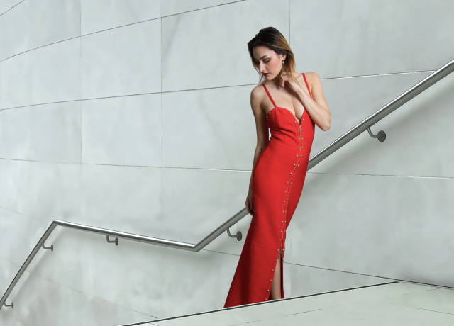 woman in red sleeveless dress standing beside white wall