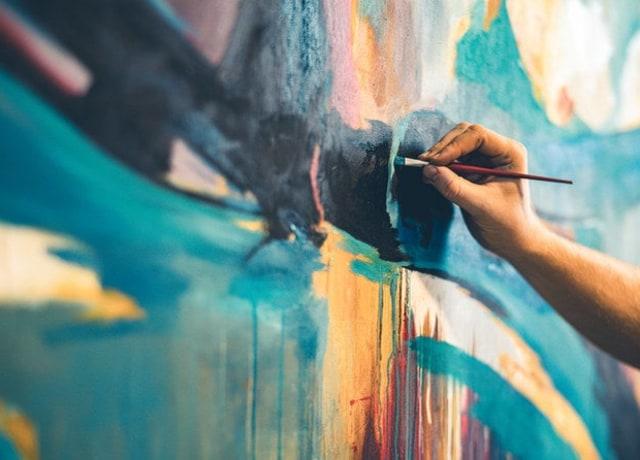 Uma pessoa pintando um mural bem colorido