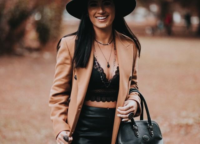 woman in brown blazer and black skirt wearing black hat