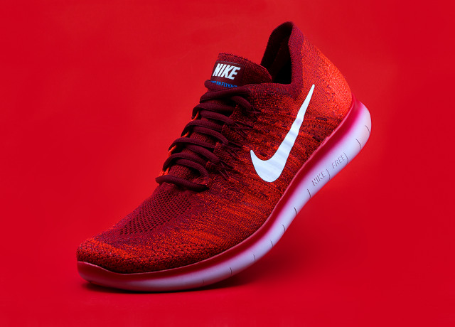 unpaired red Nike sneaker