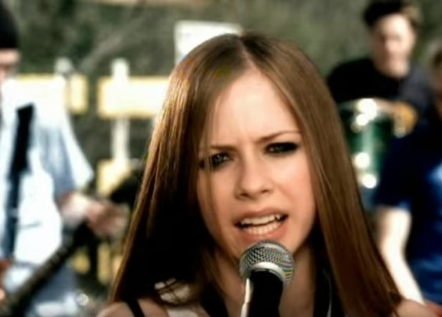 Avril Lavigne singing into the microphone with two band members in the background
